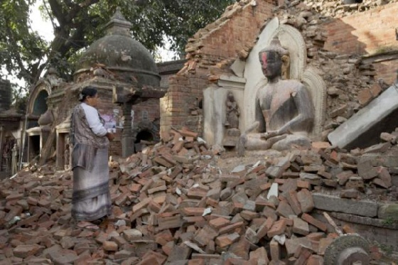 A Nepalese woman says morning prayers Saturday at a temple in Bhaktapur, Nepal, that was reduced to rubble in the April 25 earthquake. Bernat Armangue/AP
